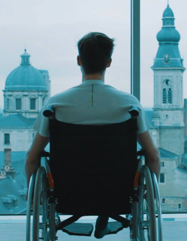 Youngster in a wheelchair looking out a large window